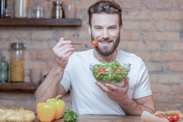 Ein Mann isst einen Salat